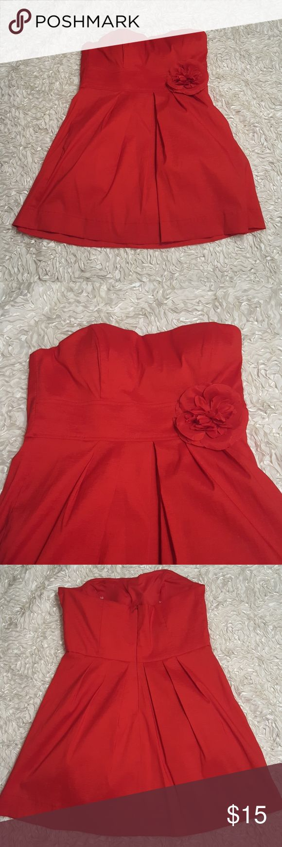 Short strapless red dress with flower pin Super cute bright red dress with flower pin on waist. Fun for a dance! Small amout of tool under skirt that gives it a little volume Blondie Nites Dresses Midi
