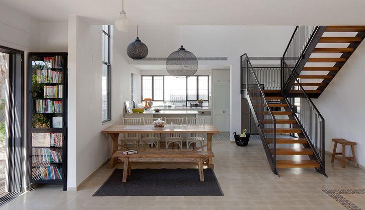 ארונות הגובה שבמטבח מוקמו מול גרם המדרגות המוביל לקומת חדרי השינה ומטשטש את מסת הנגרות שנחשפת לעיני הנכנסים. מעל שולחן האוכל נתלו שני גופי תאורה שחורים של המותג ההולנדי moooi. קומת הכניסה רוצפה באריחי בטון בגון חול. במבואה שולבה בריצוף מסגרת של אריחים מעוטרים בצבעי חום וירוק ( צילום: אלעד שריג )