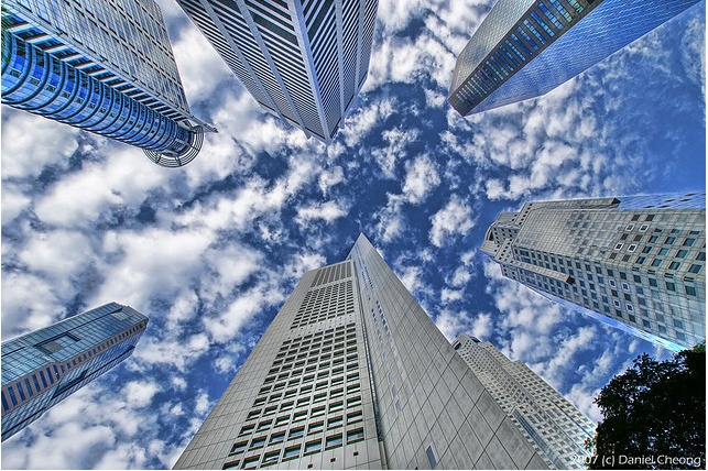 """""""Inverted Vertigo"""" by Daniel Cheong    There is something really eye-catching about the contrast in textures of this photograph. The fluffy texture of the clouds and the silky texture of the buildings provide a lot of visual interest. This photo takes a look at a familiar subject in a new way. There are millions of cityscape photos, but this one does a great job taking a new perspective. The buildings act as leading lines toward the sky sort of making the photo have a dreamy quality about…"""