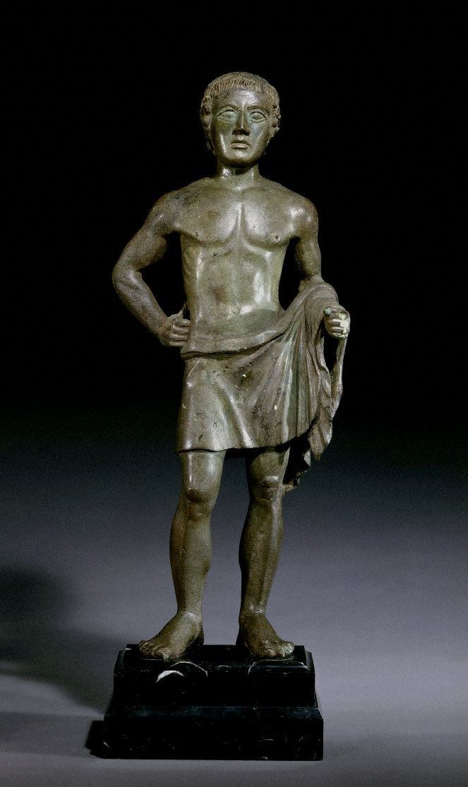 Bronze votive statuette of a youth, probably once with an offering in his left hand. Etruscan 400BC-350BC.
