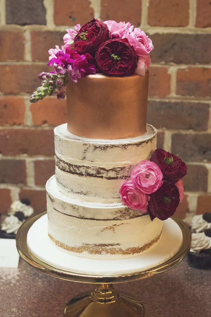 Gold semi naked wedding cake with pink and burgundy flowers | Fields & Skies