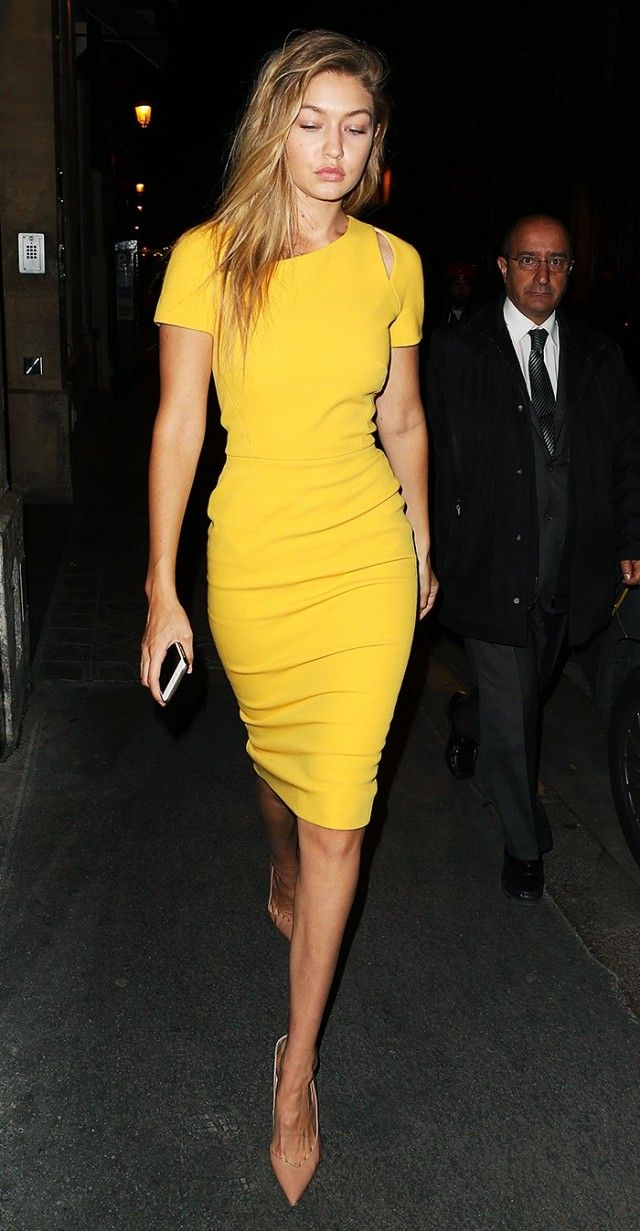 Gigi Hadid wears a body-con golden yellow dress with nude pumps