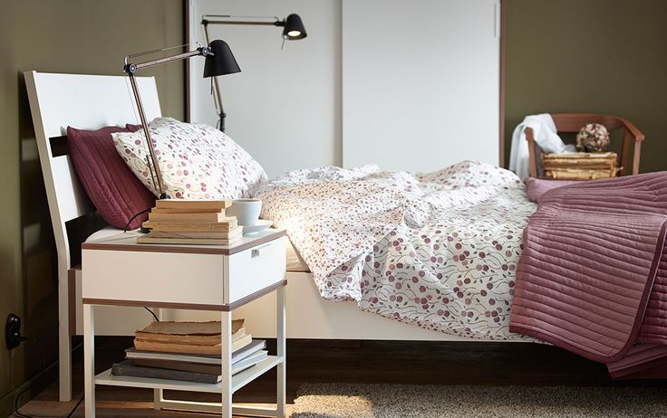 A bedroom with a bed for two, bedside tables and a wardrobe, all in white/light grey