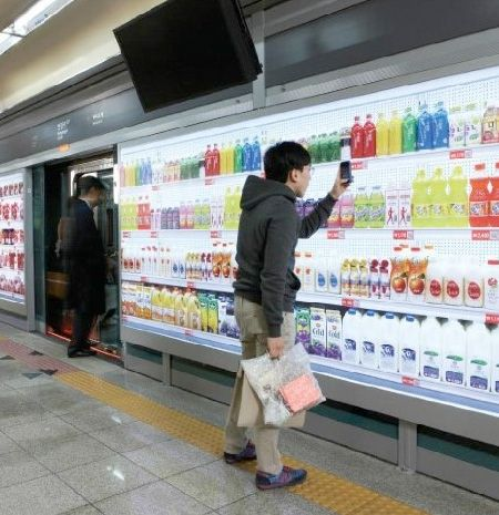 People in South Korea can now shop for groceries at Tesco Homeplus virtual stores while they wait for the subway train.   Displays with products were installed in subway stations. Customers scan QR codes with their phone, and the groceries are delivered to their home
