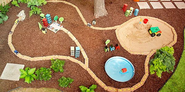 Backyard play area with with road of pavers, even includes a tunnel with PVC pipe, sandbox and water element. Love it! from Lowes