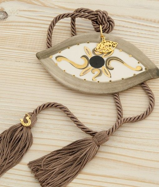 Traditional hand painted enamel eyes with gold leaf and long tassels.