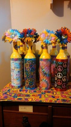 Party idea for 60s party. Spray paint wine bottles add scrap booking paper and ribbon.