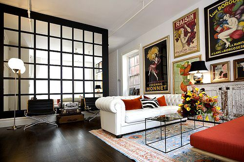 Large vintage French ad posters, white chesterfield sofa, dark hardwood floors and wall of windows. Eclectic. Fabulous