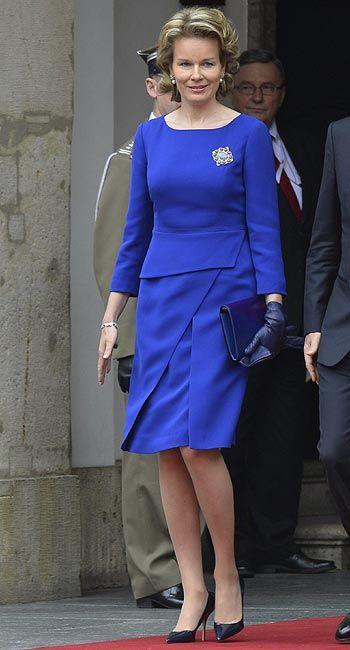 Reina Matilde de Belgica. 'Look': En su apuesta por un 'look' más juvenil, Matilde ha acudido a la capital polaca con un vestido de cóctel liso azul 'Klein'. La Reina de Bélgica hace uso de un broche con turquesas para decorar el conjunto.