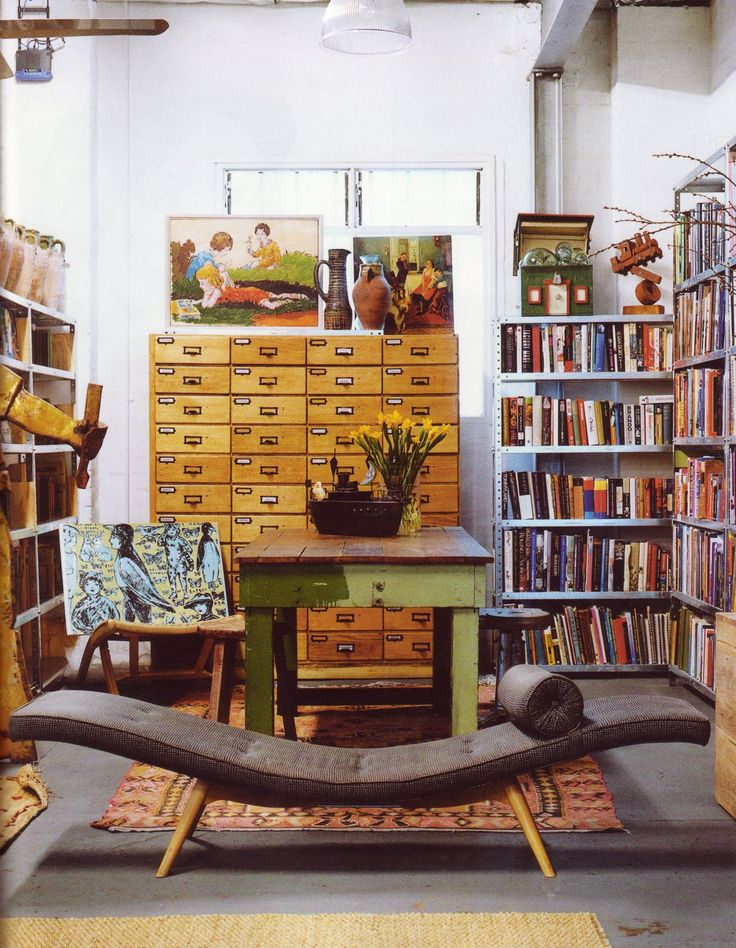 a library style room that would work as a studio space for a book lover with the addition of a daybed or sleeper sofa instead of the lounger. I like the central work table/dining table/desk idea:)
