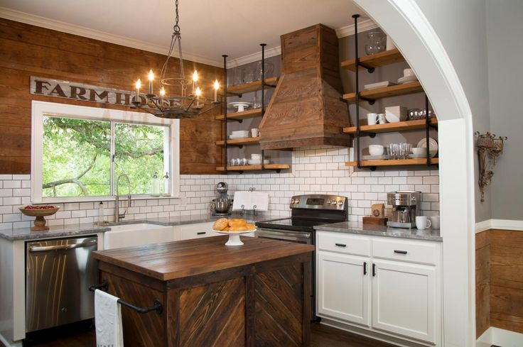 Fixer Upper hosts Chip and Joanna Gaines painted one wall a neutral gray and brought in shiplap for a feature paneled wall, matching detail in other parts of the home. A white subway tile backsplash and quartzite countertops add a modern element to the rustic space. Industrial-style shelving made from plumbing pipes and wood planks offer open storage, and a custom kitchen island made from vintage wood contributes style and utility in the kitchen.