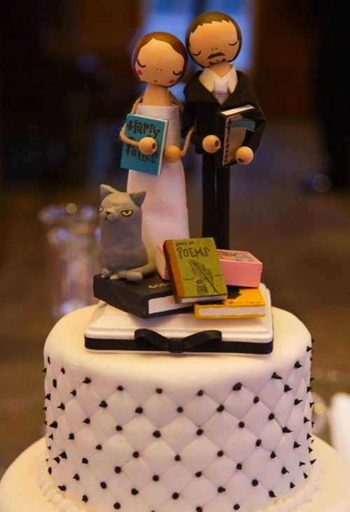 "A wedding cake topper for book lovers.  She's even holding, ""Harry Potter."""