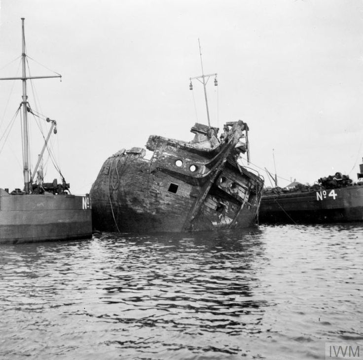 SALVAGE OF WOODEN WALLS. 8 JULY 1948, THE HULK OF HMS CORNWALL, 72 GUN SHIP OF THE LINE, BUILT AT THE END OF THE NAPOLEONIC WARS, WAS MOVED FROM THE THAMES, NEAR GRAVESEND AND BEACHED OFF GRAYS. SHE HAS RESTED IN THE MUD SINCE SHE WAS SUNK BY A NEAR MISS BOMB IN 1940. THE PORT OF LONDON AUTHORITIES REMOVED HUNDREDS OF TONS OF MUD FROM HER HOLDS, LIFTED HER OFF THE BOTTOM BY MEANS OF CAMEL, AND TOWED HER TO GRAYS FOR SALVAGE.