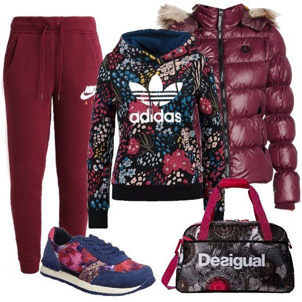 Abbigliamento sportivo, per essere alla moda anche in palestra. La felpa a fiori Adidas è indossata con pantaloni bordeaux Nike e con un pratico piumino corto che, all'occorrenza, può diventare uno smanicato. Il borsone fantasia Desigual e le bellissime scarpe in camoscio e glitter completano il look.