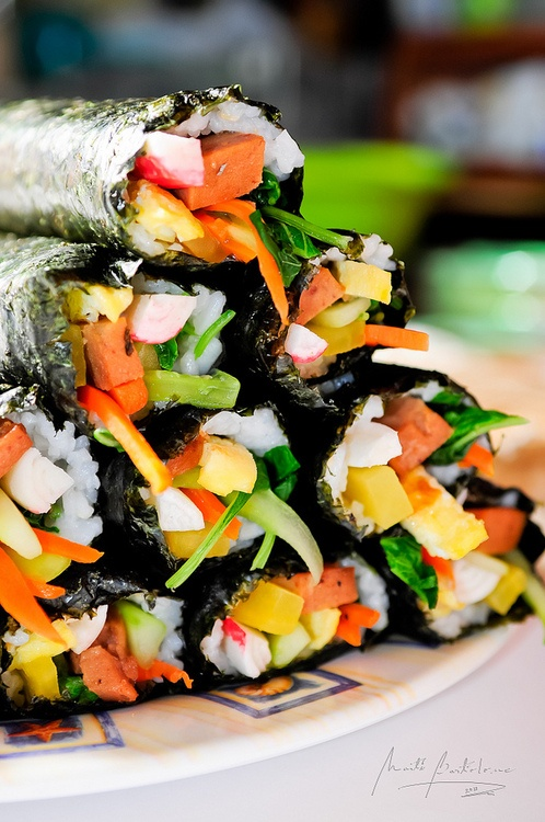 Kimbap, a Korean sushi roll (without raw seafood). My mom makes the best version! My kids (4 and 1 1/2 LOOOOOVE kim bap)! : ) She uses egg, blanched spinach with Korean seasonings, fried spam, and dakwang.