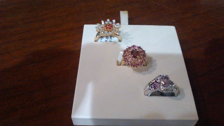From left to right diagonally: 1. a 14k yellow gold ring with 7 garnets surrounded by white color stones.       2.  a 14k yellow gold ring adorned with 3 carats of pink sapphires    and 3.  14k white gold ring with light purple color stones.
