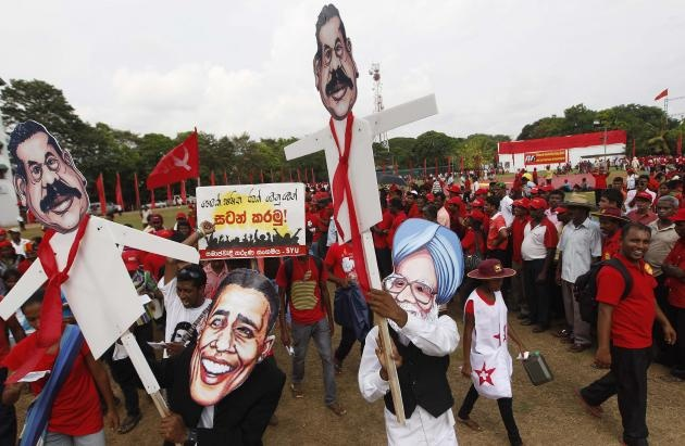 A supporter of Democratic National Alliance opposition party wears mask of Indias PM Singh as he holds puppet of Sri Lankas President Rajapaksa at May Day rally march in Colombo