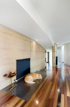 A rammed earth wall forms the spine of this home in Melbourne, Australia. The dirt was sourced mostly from a local quarry for its yellow-orange color. Mihaly Slocombe, Architects.