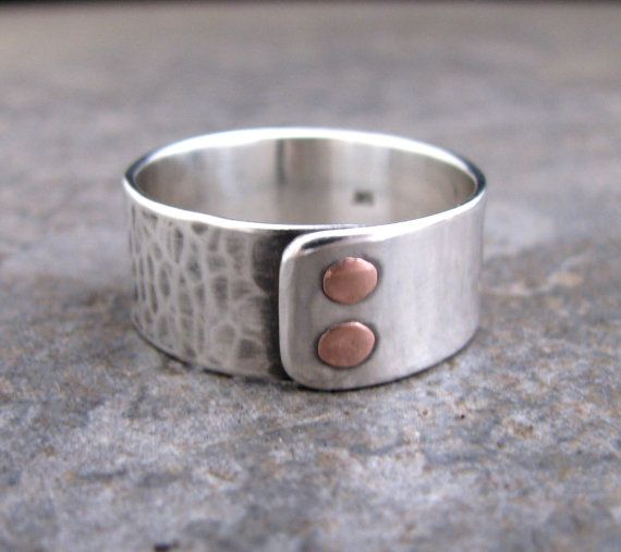 This is a handmade and hand-textured sterling silver ring with 2 handmade copper wire rivets.    I gave half of the ring a hammered and