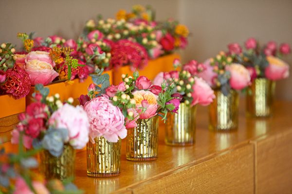 Orange and pink flowers in small vintage style vases.  From 'Ian Stuart and Sparkly Kate Spade's For A Bright and Colourful Spring Time Wedding' on www.lovemydress.net.  Photography by http://www.novaweddingphotography.co.uk/  Photography by http://www.novaweddingphotography.co.uk/