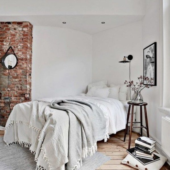 Layered, cozy blankets and minimalist wood and brick accents bring out the hygge in this bedroom. Scandinavian bedroom design by gothenburg interior designer INTRO INRED #rustic #Scandi #Scandinavian #hygge #decor