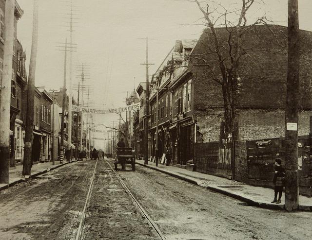 Montréal 1904. Rue Notre-Dame >Est, depuis rue Napoléon.      Arch. STM.  Un charrettier longe la rue Notre-Dame vers la rue Vinet. On voit une ligne de tramway. La rue est en terre battue. Certains de ces bâtiments sont encore là aujourd'hui.  La rue Napoléon est l'ancien nom de la rue Charlevoix  Comparatif du 16 mars 2011 www.flickr.com/photos/urbexplo/5545403451