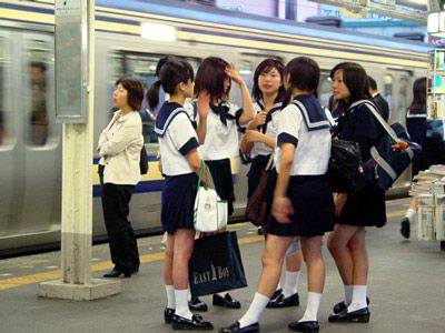 Japanese school girls hanging out in subway station.