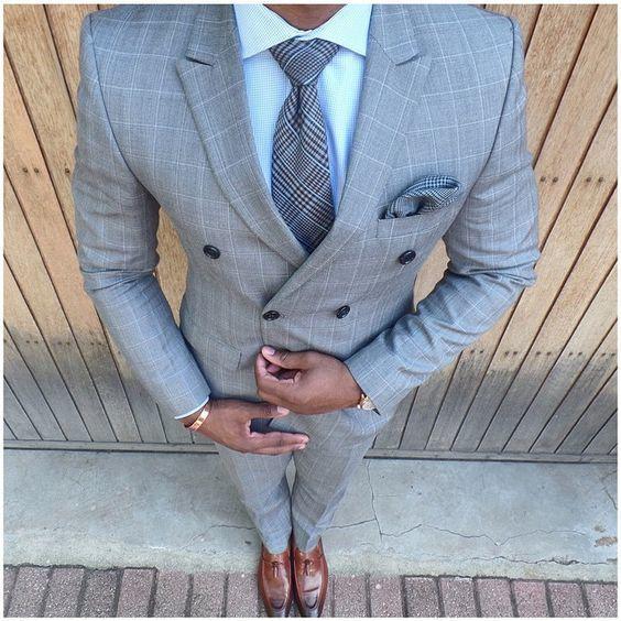 Acheter la tenue sur Lookastic: https://lookastic.fr/mode-homme/tenues/blazer-croise-chemise-de-ville-pantalon-de-costume/18844   — Chemise de ville bleue claire  — Cravate écossais gris  — Pochette de costume écossais gris  — Blazer croisé à carreaux gris  — Pantalon de costume à carreaux gris  — Mocassins à pampilles en cuir bruns