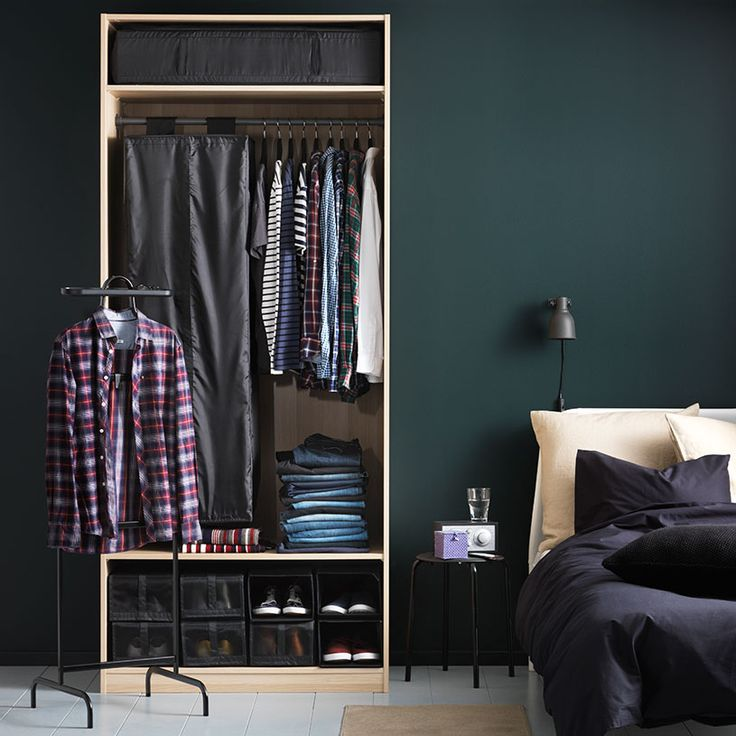 A bedroom with an open wardrobe filled with storage boxes, clothes tidy, clothes hanger and shoe boxes