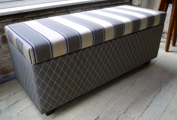 Padded ottoman with hinged lid for storage.