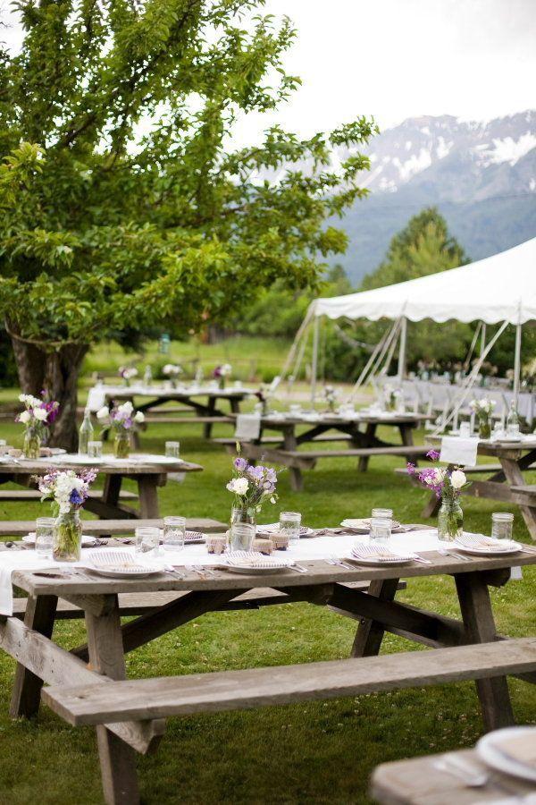 Boda tipo picnic con mesas y bancos de madera