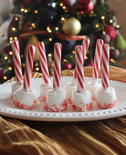 Hot chocolate stir sticks made with peppermint sticks, marshmallows, white chocolate, and red candy sprinkles.