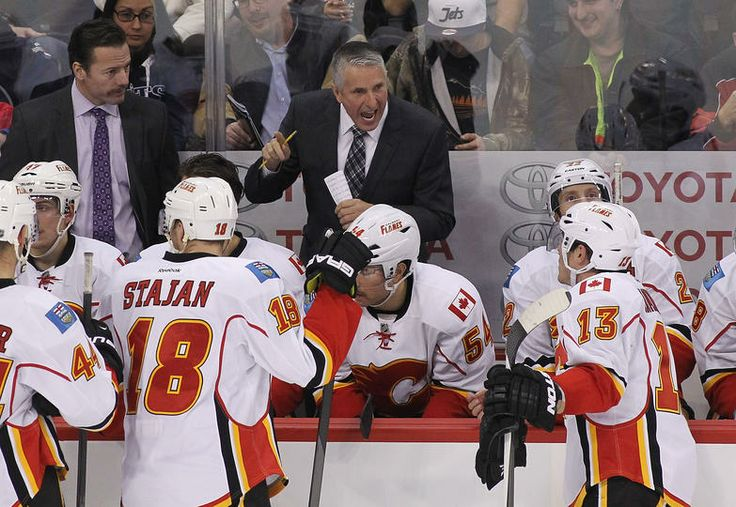 WINNIPEG, MB - NOVEMBER 18: Bob Hartley, head coach of the Calgary Flames, talks to his team during a break in overtime action in an NHL game against the Winnipeg Jets at the MTS Centre on November 18, 2013 in Winnipeg, Manitoba, Canada.