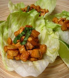 Thai Tofu Lettuce Wraps  1 small Thai pepper, minced  1 garlic clove, minced  1 Tbsp. olive oil  3 Tbsp. soy sauce  1/4 cup water  Juice of 1 lime (plus more for garnish)  1 Tbsp. arrowroot powder or cornstarch  2 Tbsp. vegetable oil  1 16-oz. pkg. firm tofu, drained and cut into 1/4-inch pieces  1 Tbsp. basil, finely chopped (plus more for garnish)  8 iceberg lettuce leaves
