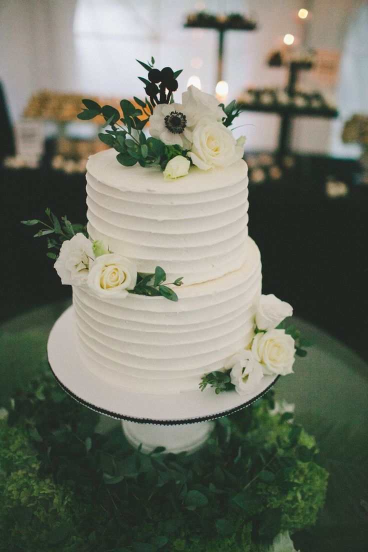 Simple two-tier wedding cake covered in real blossoms and greenery! The cake is chocolate filled with layers of marshmallow fluff and marshmallow flavoured buttercream!