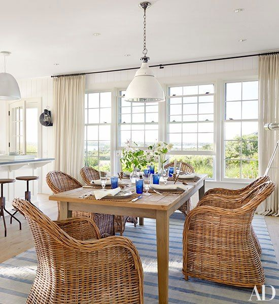 The dining area contains an Ann-Morris white enamel pendant light, wicker chairs by Circa Antiques, and a Swedish table; the vintage dhurrie is from Madeline Weinrib.
