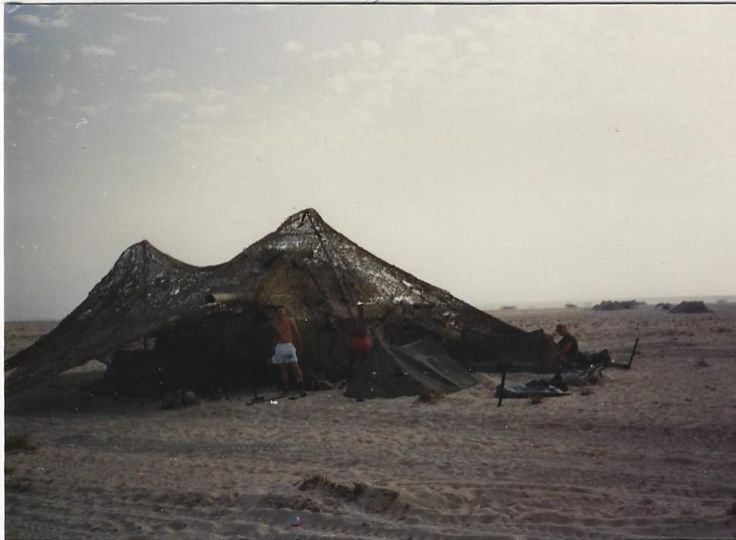 Tank in camouflage netting after the sandstorm. Operation Desert Shield.