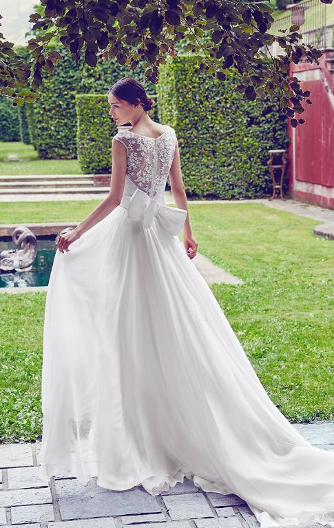 Elegant cap sleeve lace back wedding dress with statement bow; Featured Dress: Giuseppe Papini