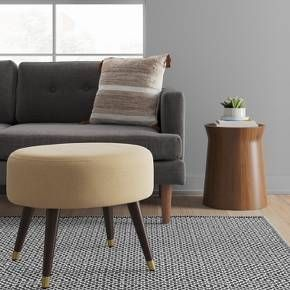 With a hint of metallic shine at the tips of its sleek tapered legs, this oval ottoman is a chic addition to the front of your favorite chair – or off to the side as an impromptu extra seat. Softly cushioned and hand-upholstered in a fabric of your choice, this mid-century classic is one of a kind.