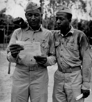 """First African American Marines decorated by the famed Second Marine Division somewhere in the Pacific (left to right) Staff Sgt Timerlate Kirven...and Cpl. Samuel J. Love, Sr... They received Purple Hearts for wounds received in the Battle of Saipan..."""