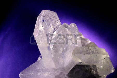 Quartz crystal illuminated on a purple background