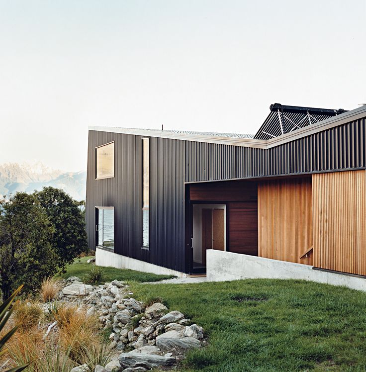 """The home is mostly clad in black trapezoidal-profile steel, with cedar boards lining what the owners call the """"human spaces""""—external passages between buildings. A solar hot water system perches on the roof."""