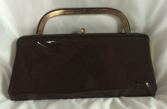 Vintage brown patent leather clutch with gold handle and hardware. The interior has a beige silk lining.