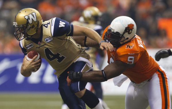 Winnipeg Blue Bombers quarterback Buck Pierce (L) is sacked by BC Lions defensive end Keron Williams during the first half of their CFL football game in Vancouver, British Columbia, June 29, 2012.Quarterback Bucks, Lion Defense, Keron Williams, Bomber Quarterback, Bucks Piercing, Football Games, Cfl Football, Blue Bomber, British Columbia