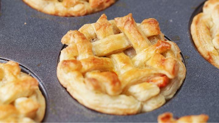 12個分材料オリーブオイル 大さじ1 鶏むね肉(一口大) 680g バター 60g玉ねぎ(角切り)1個にんじん(角切り)3本 薄力粉 60g牛乳 240mlチキンスープ 480ml冷凍グリーンピース 1カップ塩 小さじ1コショウ 小さじ1/2パイシート 4枚溶き卵 適量作り方1. オーブンは220℃に予熱しておく。2. 鍋にオリーブオイルを引いて強火で熱し、鶏むね肉を入れて7分ほど炒めたら、皿などに取り出す。3. そのままの鍋にバターを入れて溶かしたら、玉ねぎとにんじんを加えて、柔らかくなるまで8分ほど炒める。4. 薄力粉を加えて混ぜ、全体になじんだら牛乳とチキンスープを少しずつ加えてのばし、ひと煮立ちさせる。5. (2)を戻し入れ、グリーンピース、塩・コショウを加えて混ぜたら火から下ろす。6. パイシートを直径16cmほどに切り抜き、マフィン型にはめたら、粗熱をとった(5)を入れる。7. 残りのパイシートを3mm幅に細長く切り分け、(6)の上に少し隙間をあけて格子状にのせ、交互に編み込む。8…