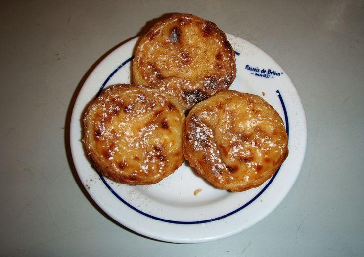 Pastéis de Belem - via Saudades de Portugal 27.05.2015 | Je zou het niet verwachten, maar het is waar: de pastéis van Belém zijn echt honderd keer lekkerder dan de andere pastéis de nata die je kunt kopen in de Portugese supermarkten en cafés. Nu is het natuurlijk sowieso een lekker gebakje. Krokant bakje, romige pudding… heerlijk voor bij een kopje koffie of thee. Maar als je aan één van de vele tafeltjes zit van de confeitaria in Belém en ze warm voor je worden neergezet en je de kaneel en…