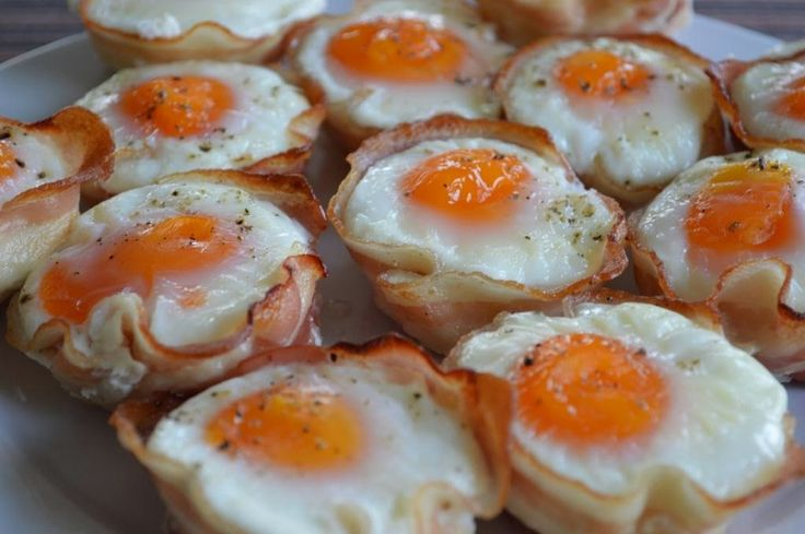 Ei-muffin met spek - 6 plakken spek - 6 eieren - 40 gr gesnipperde ui - 30 gr gesnipperde rode (punt)paprika - peper - handvol verse bieslook - boter om in te vetten Bereiding: Vet een muffin-vorm goed in met boter. Bedek de bodem en de rand van de vormpjes met het spek. Verdeel hierover de ui en paprika. Maal er verse peper over. Breek boven iedere opening een ei kapot. Strooi wat gesnipperde verse bieslook over ieder eitje. Zet de muffins 20 minuten op 180 °C in een voorverwarmde oven.