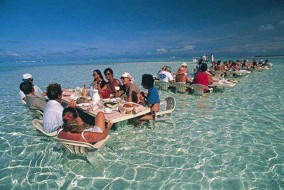 Restaurant in Bora Bora - Restaurant tables and chairs in shallow ocean water in Bora Bora.