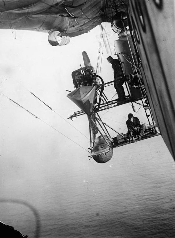 Three members of crew at work on the starboard engine gantry of a Royal Navy Air Service North Sea (N.S.) type non-rigid airship during an anti-submarine patrol off the British coast circa 1918. None appear to be wearing a safety line. On the upper level the mechanic is standing next to his compartment from which he controlled the 240HP Fiat engines. On the lower level a gunner mans his gun.   www.airshipcenter.com