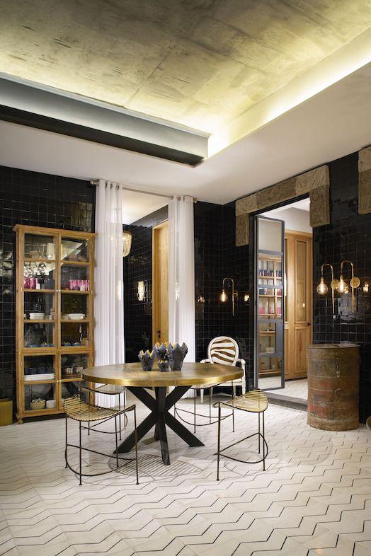 Este antecomedor moderno pero vintage a la vez es un sueño. El librero de madera y vidrio se utiliza para guardar platos y jarrones. las paredes negras dan un look sofisticado y elegante.